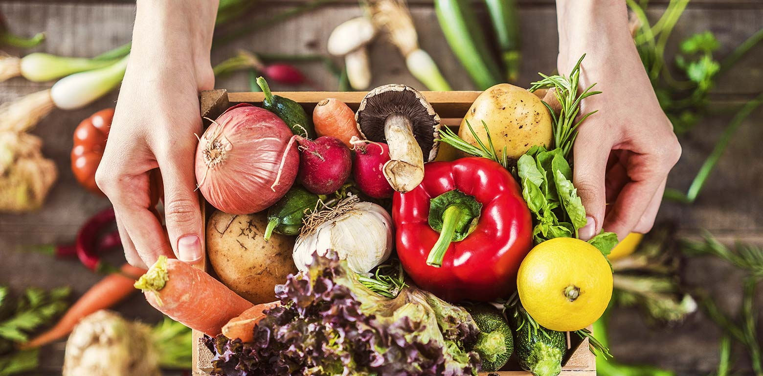 A box of vegetables held up by a woman